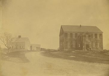 Exterior view of the Rocky Hill Meeting House and Parsonage, Amesbury, Mass. Two men are gatehred near the front doorway.
